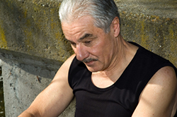 Older male leaning against wall, anxious